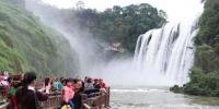 图为游客在黄果树瀑布前合影。 贺俊怡 摄 - 贵州新闻